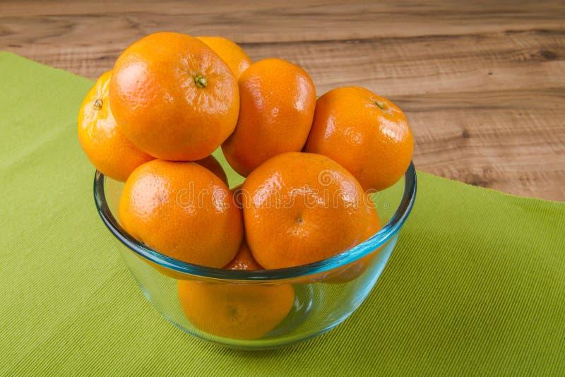 Mandarini freschi in piatto trasparente su una tovaglia verde, tavola di legno fotografie stock