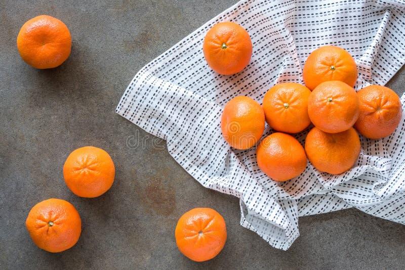 Mandarini sparsi attraverso la Tabella immagine stock