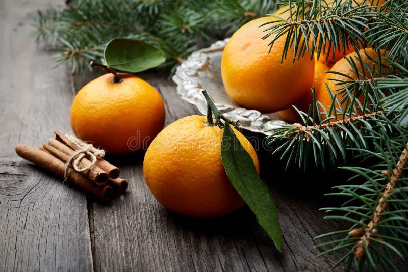 Mandarini in vaso d'annata del metallo e rami degli aghi del pino su un fondo di legno fotografia stock