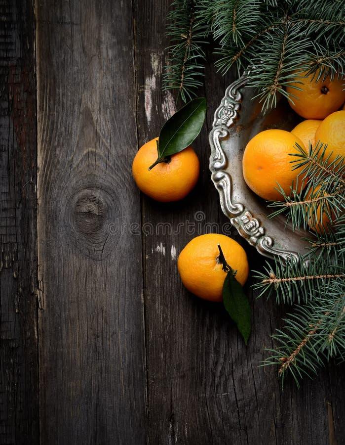 Mandarini in vaso d'annata del metallo su un fondo di legno fotografie stock