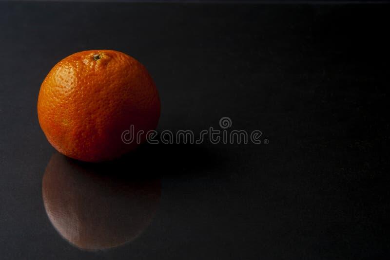 Mandarino isolato sul fondo del nero scuro con il reflectio fotografia stock libera da diritti