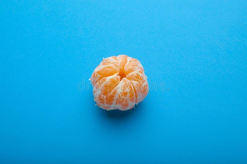 Mandarino sbucciato del mandarino isolato su un fondo blu fotografia stock libera da diritti