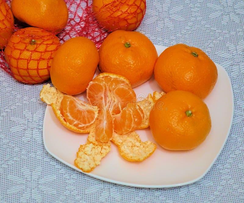 Mandarino sbucciato diviso nelle fette su un piatto bianco immagini stock libere da diritti