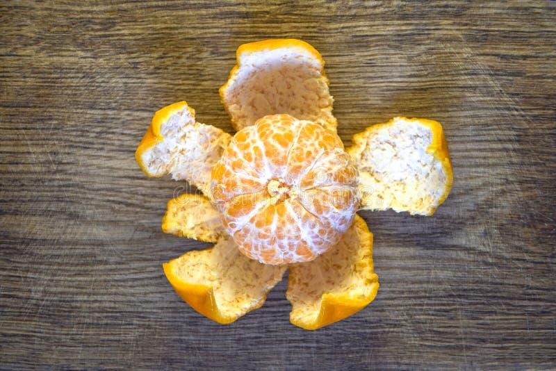 Mandarino sbucciato sulla buccia sotto forma di fiore su un vecchio bordo della quercia fotografia stock