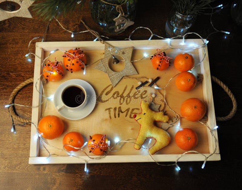 Mandarins, koffie, decoratie en slinger op een houten dienblad met gegraveerd stock afbeeldingen