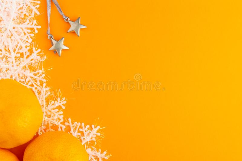 Mandarins, silver toy stars and snowflakes on a orange background. Winter Holiday festive greeting card with copy space for the. Text. Xmas flat lay concept stock photography