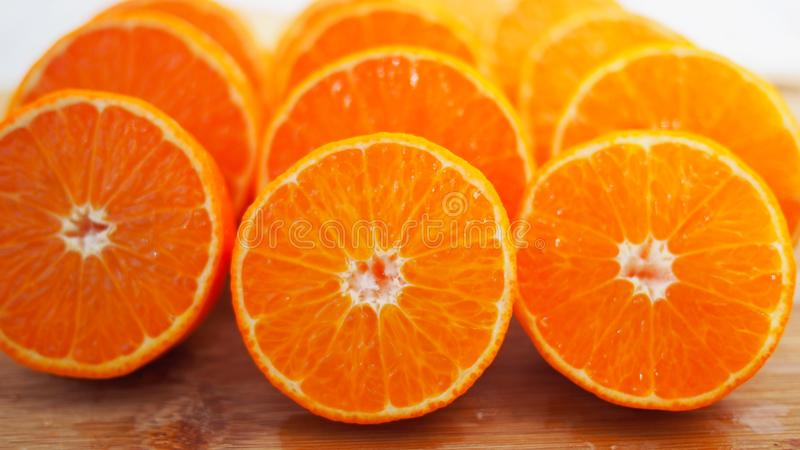Mandarins, voor sap wordt gesneden dat Vruchten van mandarin, besnoeiing, op houten achtergrond royalty-vrije stock afbeeldingen