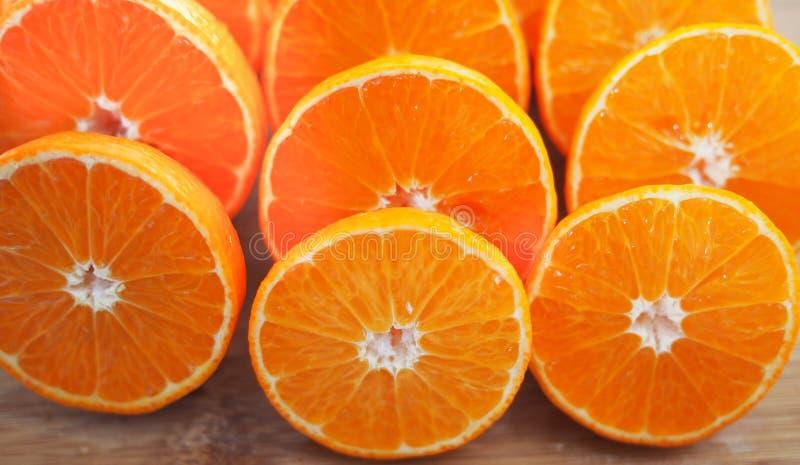 Mandarins, voor sap wordt gesneden dat Vruchten van mandarin, besnoeiing, op houten achtergrond stock afbeeldingen