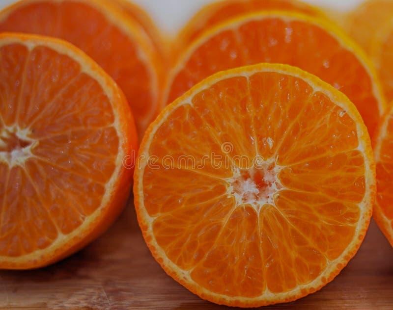 Mandarins, voor sap wordt gesneden dat Vruchten van mandarin, besnoeiing, op houten achtergrond stock fotografie