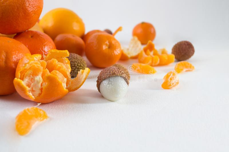 Mandarins on a white background with lobule, peel, citron and litchi. Side view, close. Citrus reticulata. Litchi chinensis.  stock images