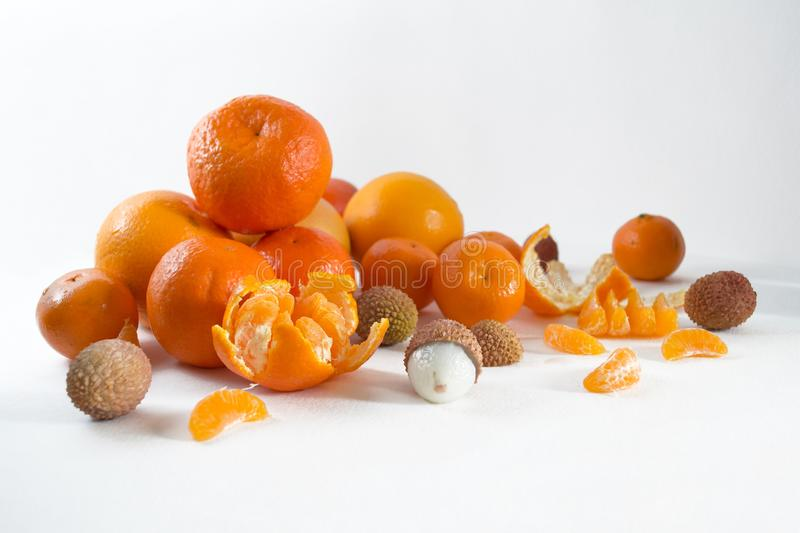 Mandarins on a white background with lobule, peel, citron and litchi. Side view, close. Citrus reticulata. Litchi chinensis.  royalty free stock photos