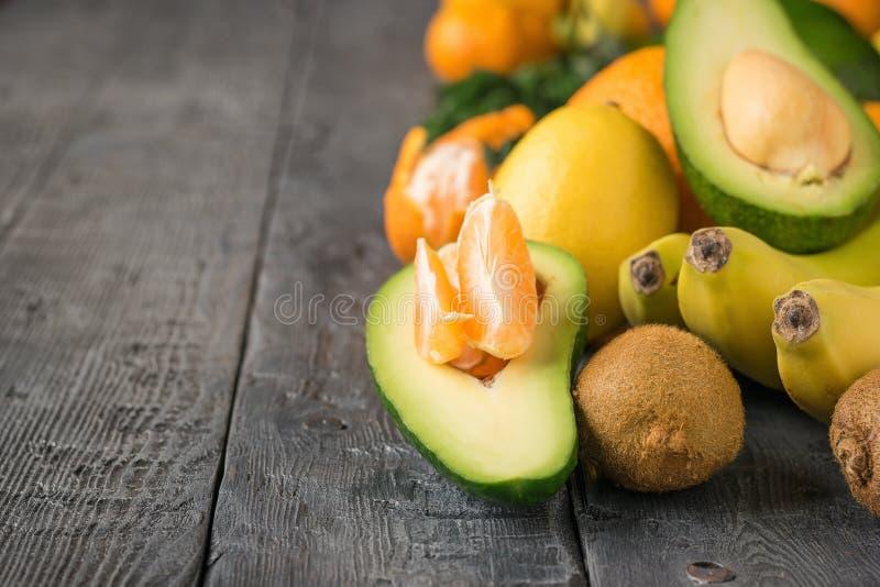 Mandarinskivorna inom en halv avokado och annan tropisk frukt på en trätabell arkivbild