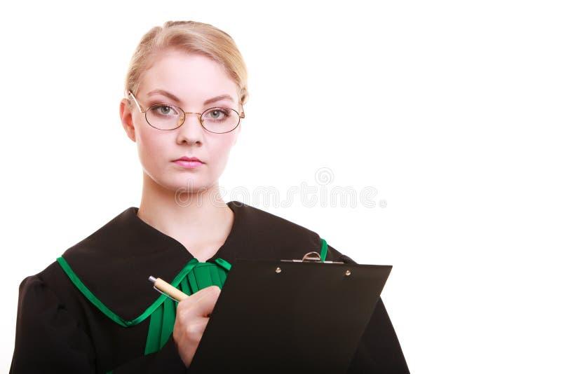 Mandataire d'avocate de femme dans l'écriture de robe de poli de classique sur le presse-papiers photo libre de droits