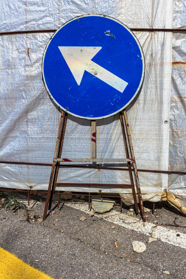 Mandatory direction sign. Old mandatory direction sign with scratches and dents in construction site stock image