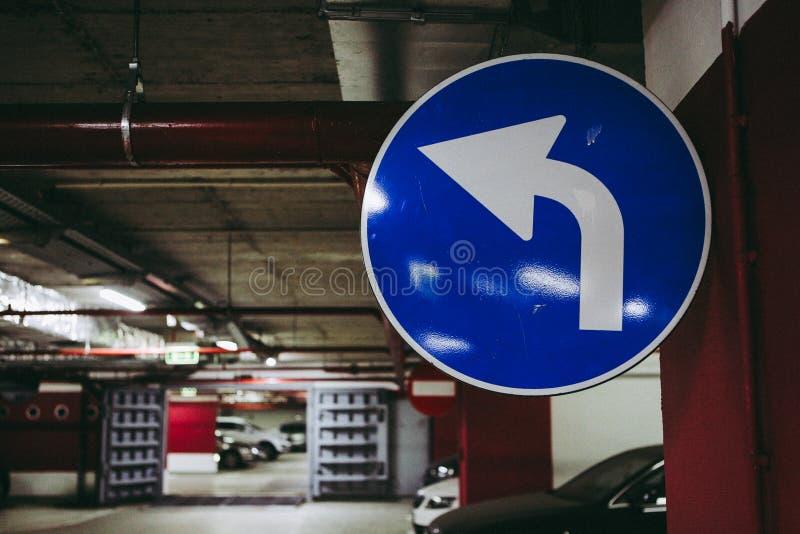 Mandatory turn left road signal inside an underground parking.  stock image