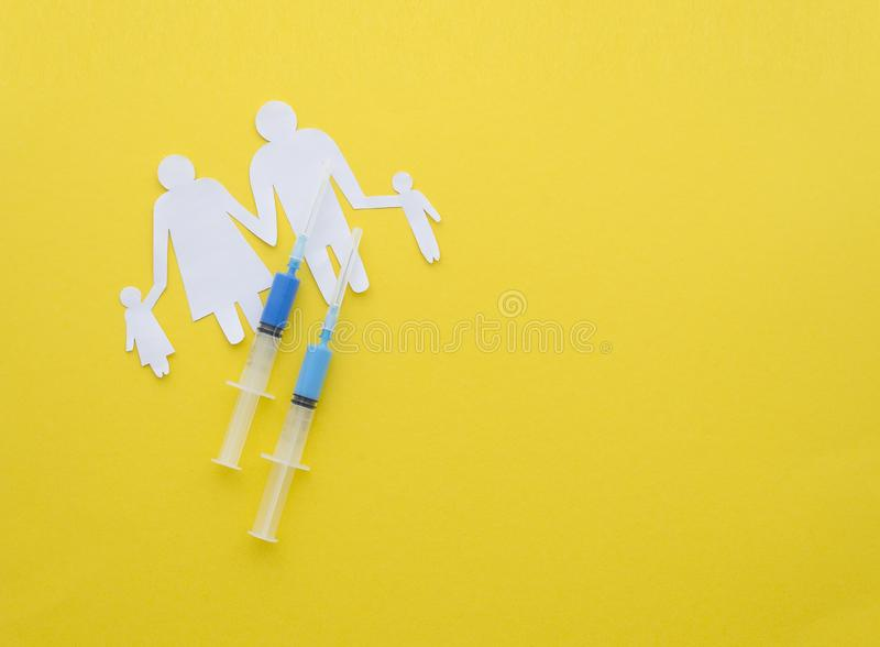 Mandatory vaccinations of children.Vaccination for healthy family. vaccination of children. Flu. Syringe near paper. Cutout family on yellow background top view royalty free stock photography