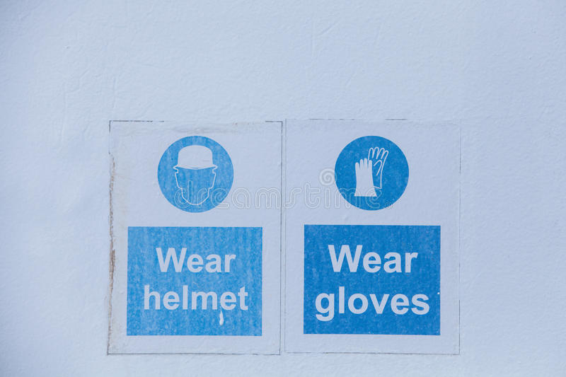 Mandatory wearing of helmets and gloves. Close up shot of some signs with mandatory helmet and gloves royalty free stock photo