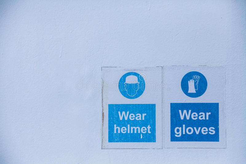 Mandatory wearing of helmets and gloves. Close up shot of some signs with mandatory helmet and gloves stock images