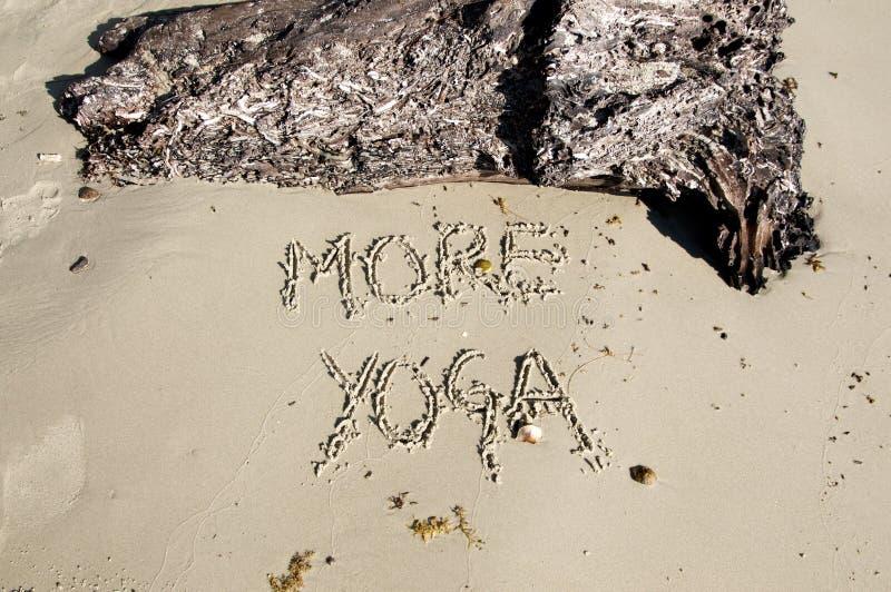 Mande un SMS a 'más yoga 'escrita en la arena en un día soleado fotos de archivo libres de regalías