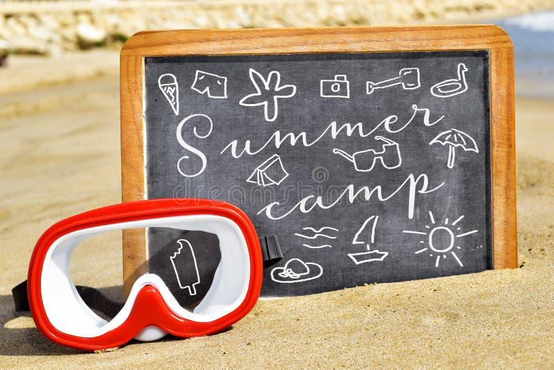 Mande un SMS al campamento de verano en una pizarra en la playa fotografía de archivo