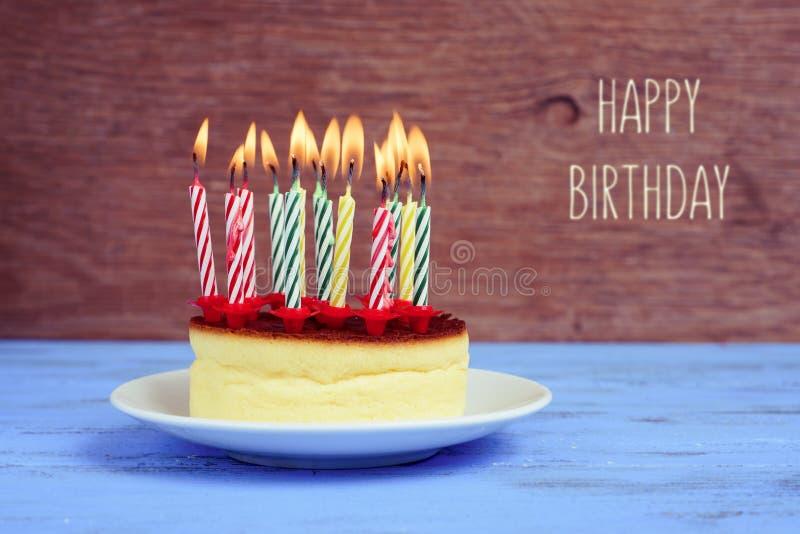 Mande un SMS al feliz cumpleaños y al pastel de queso con las velas encendidas foto de archivo