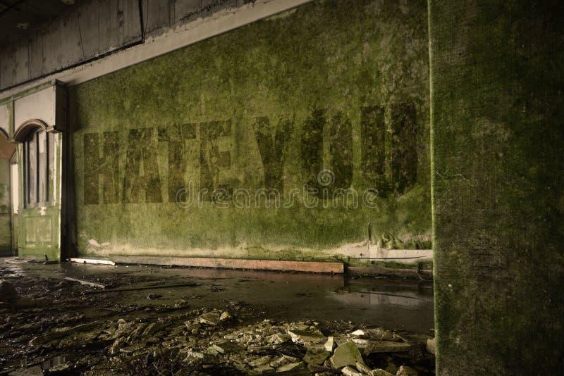 Mande un SMS al odio usted en la pared sucia en una casa arruinada abandonada foto de archivo
