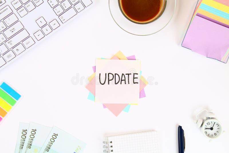 Mande un SMS a la actualización en la nota de la etiqueta engomada sobre la mesa blanca al lado de la taza y del teclado de café  fotografía de archivo