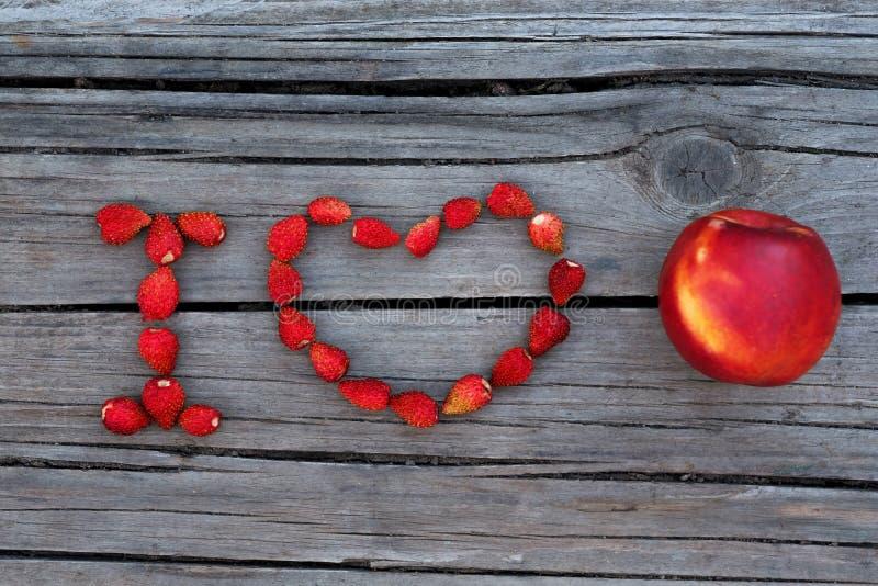 Mande un SMS a la nectarina o a las frutas del amor de I en fondo gris de madera foto de archivo