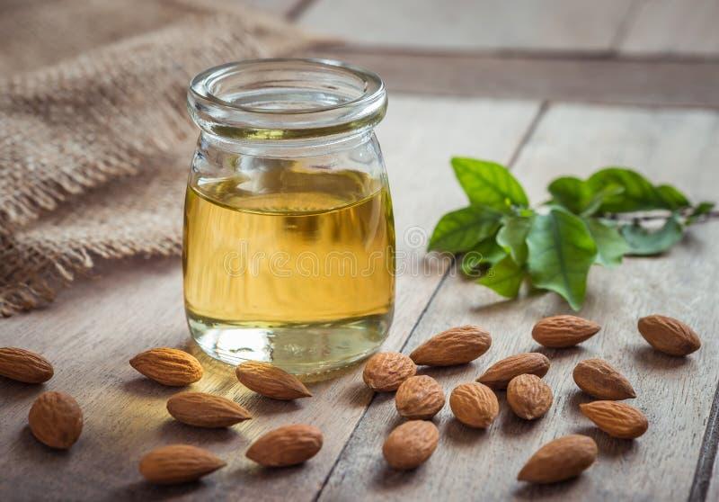 Mandelöl in der Glasflasche und in den Mandeln auf Holztisch stockfotos