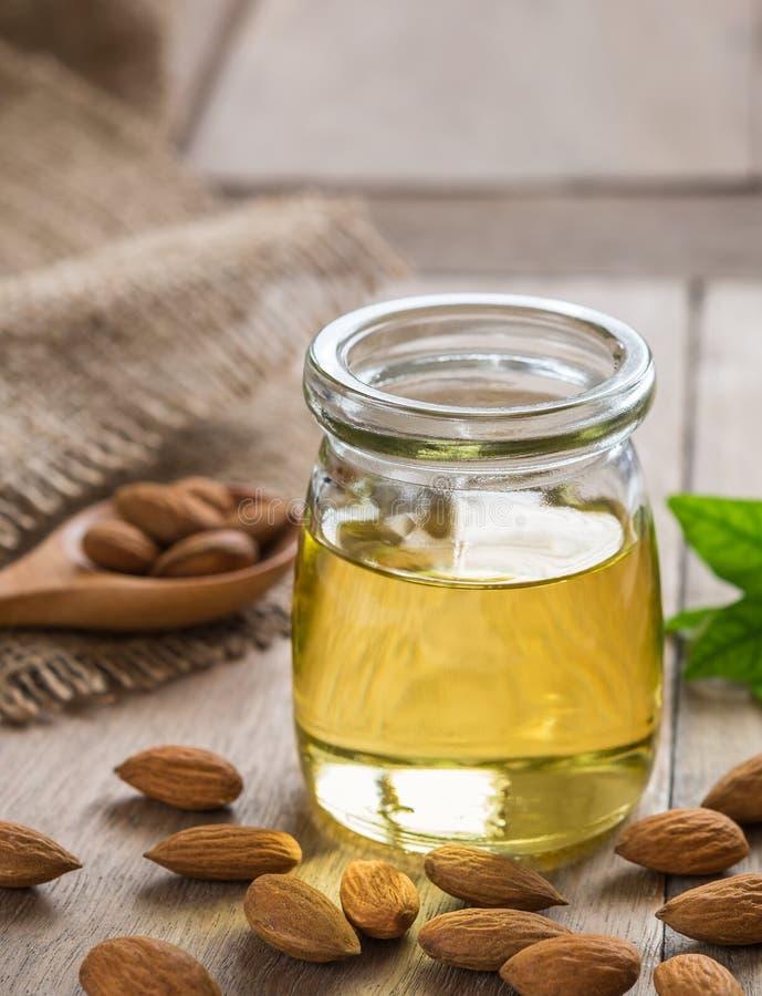 Mandelöl in der Glasflasche und in den Mandeln auf Holztisch lizenzfreies stockfoto