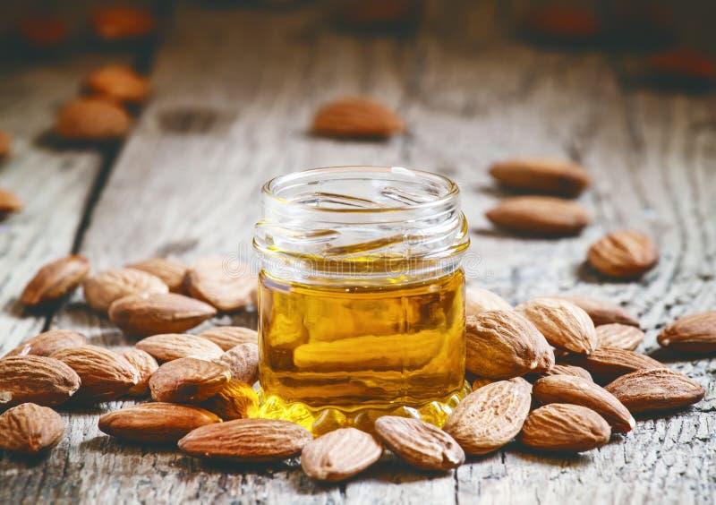 Mandelöl in einem kleinen Glas Mandeln und Nüssen auf einem alten hölzernen b lizenzfreie stockfotografie