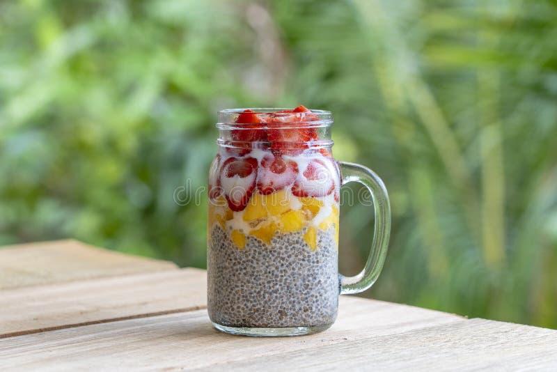 Mandelmilch chia Pudding mit frischen Erdbeeren und Mango in einem Glasgefäßbecher Chia-Samen Frühstück des strengen Vegetari lizenzfreie stockfotografie