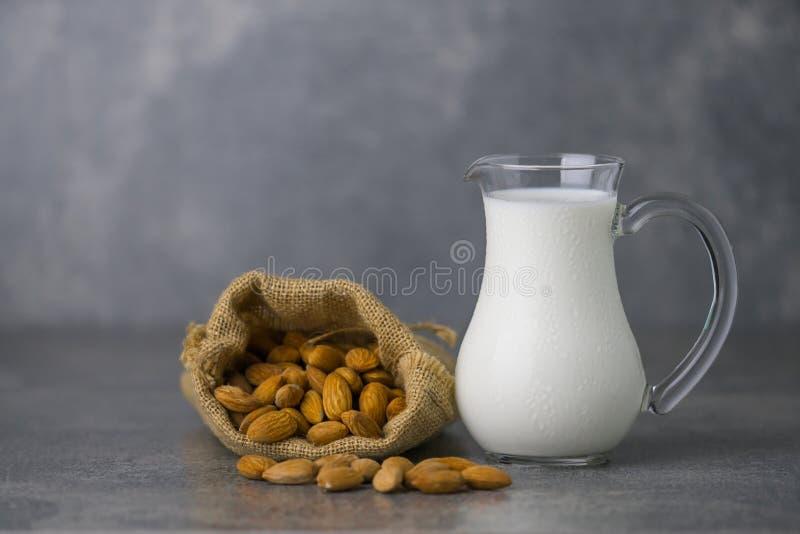 Mandelmilch im Glas mit Mandeln im Sackleinen stockfotografie