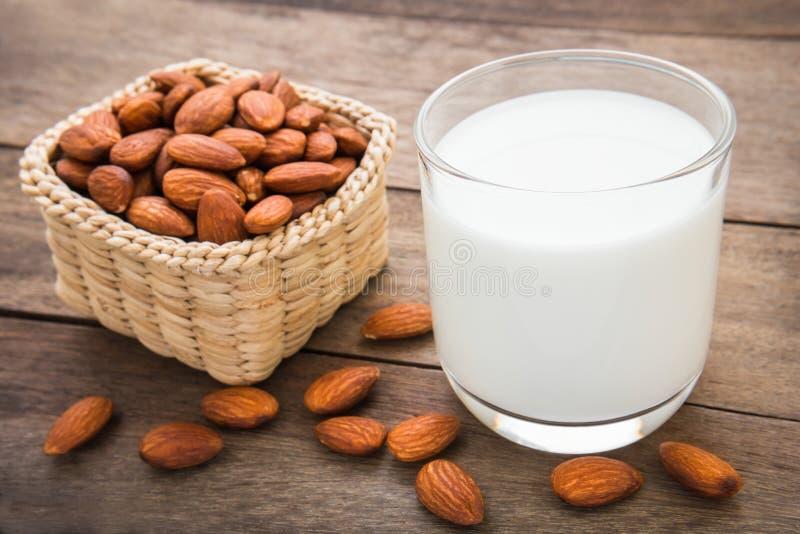 Mandeln mjölkar i exponeringsglas med mandlar på trätabellen royaltyfria foton
