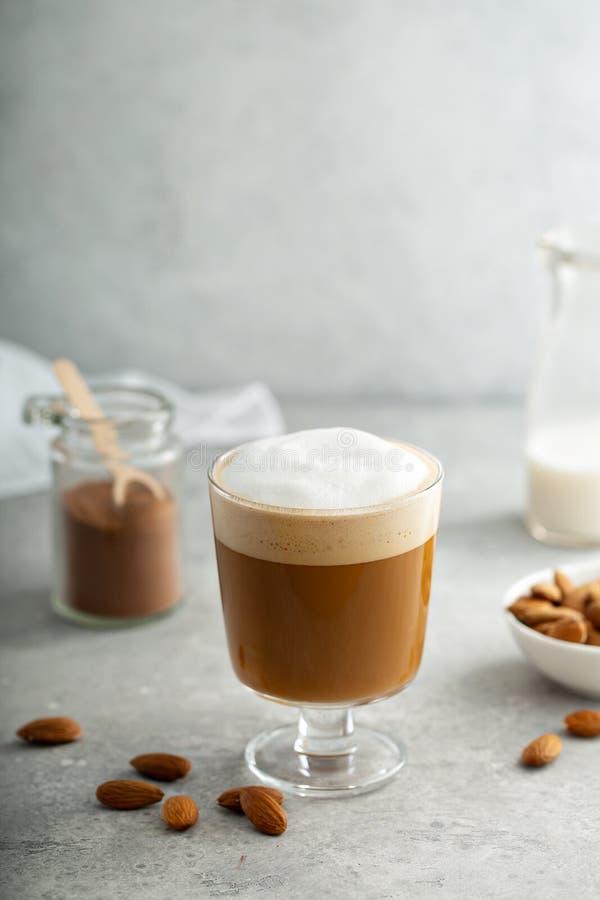 Mandeln mjölkar latte i ett exponeringsglas royaltyfria foton