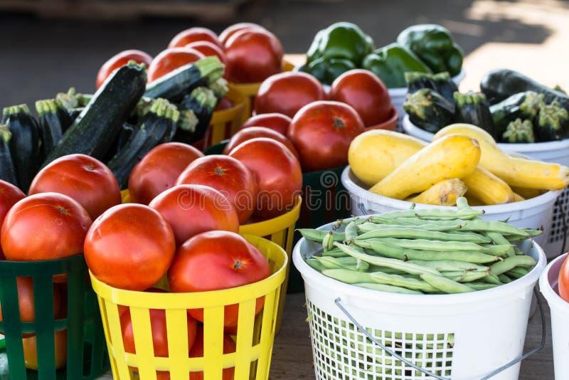 Manden van Groenten voor Verkoop bij Landbouwersmarkt stock foto's