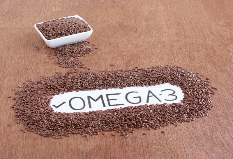 Mandi un sms al ` del ` Omega-3 scritto a mano su una carta circondata dal seme di lino immagine stock