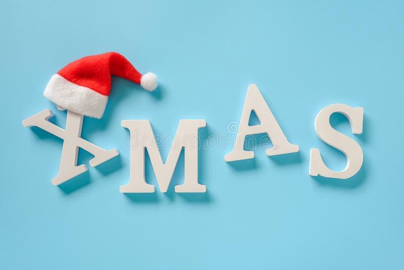 Mandi un sms al natale dalle lettere bianche del volume e dal cappello rosso di Santa su fondo blu Buon Natale di concetto Dispos immagini stock
