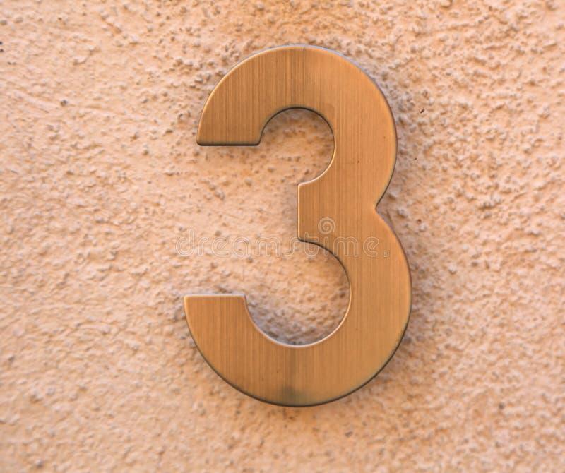 Mandi un sms al numero 3 in metallo dorato fotografia stock