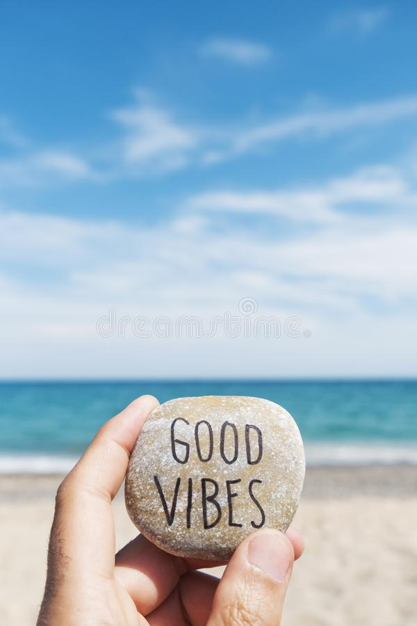 Mandi un sms alle buone vibrazioni in una pietra sulla spiaggia immagine stock