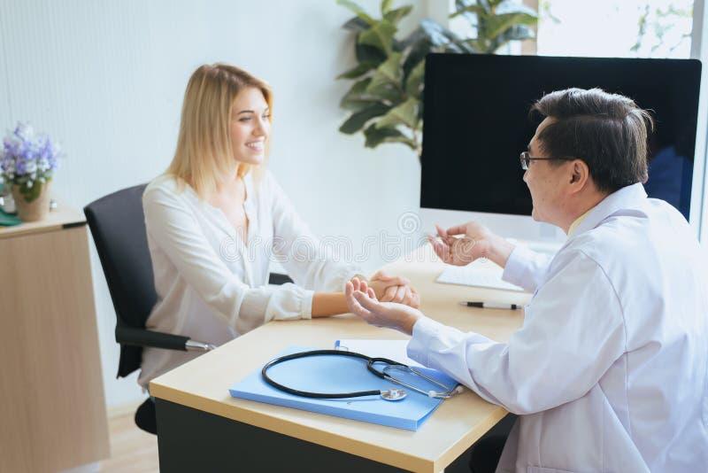 Mandoktor som undersöker till kvinnapatienten, ofruktbarhetrådgivningen och förslaget genom att använda ny teknik, läkare som ger royaltyfria foton