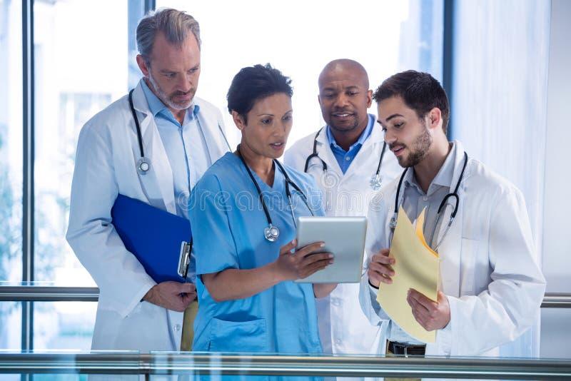 Mandoktorer och sjuksköterska som använder den digitala minnestavlan i korridor arkivfoton
