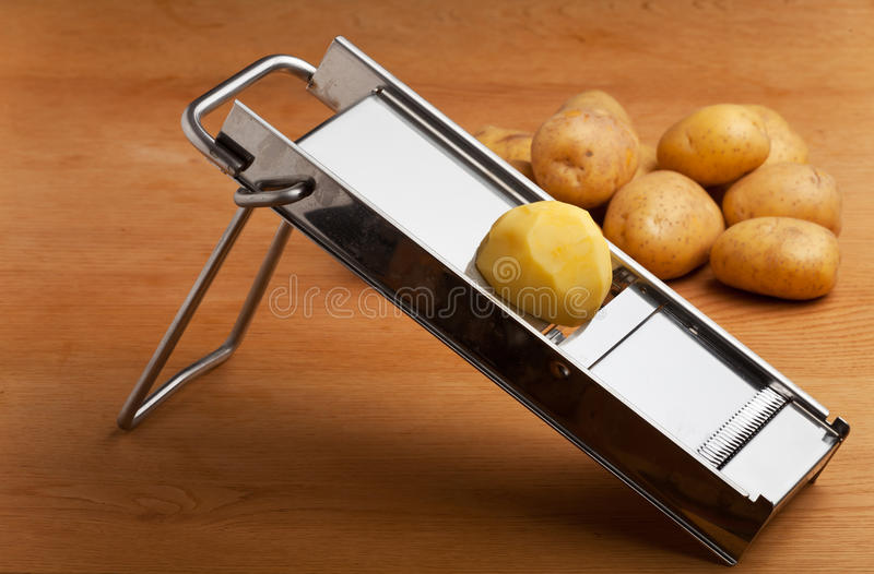 Mandolin. Half a potato on a mandolin slicer royalty free stock photography