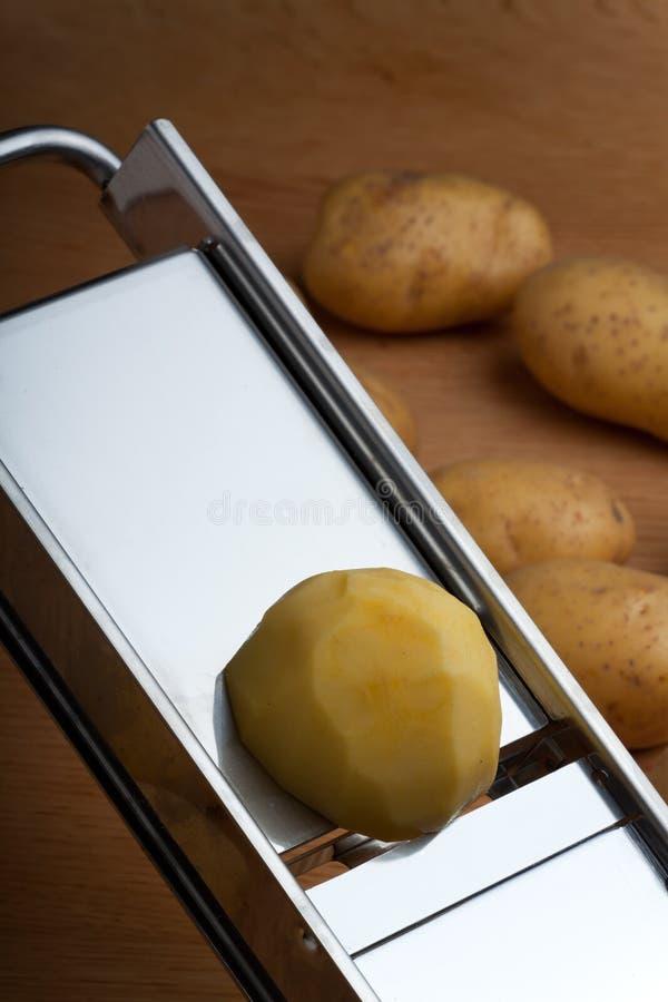 Mandolin. Half a potato on a mandolin slicer stock images