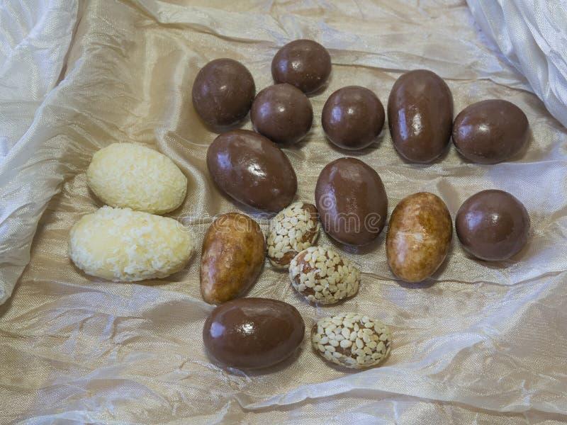 Mandorle e dadi in bianco e sesamo e noce di cocco del cioccolato al latte fotografie stock