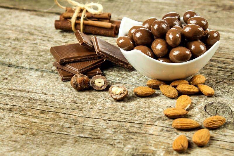 Mandorle nella glassa del cioccolato su una vecchia tavola di legno Alimento non sano Rischio di obesità e di diabete Noci dolci  immagine stock libera da diritti