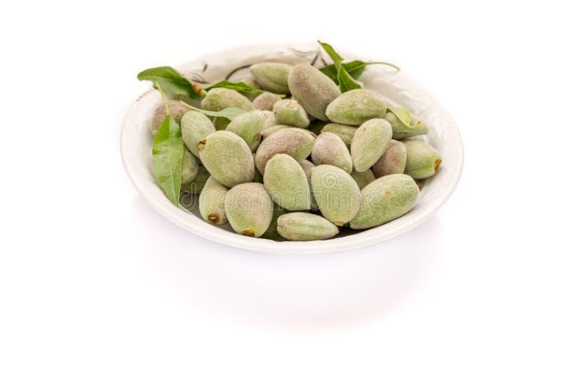 Mandorle non mature verdi fresche in piatto con fondo bianco fotografia stock libera da diritti