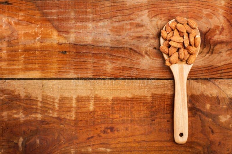 Mandorle in un cucchiaio di legno fotografia stock libera da diritti