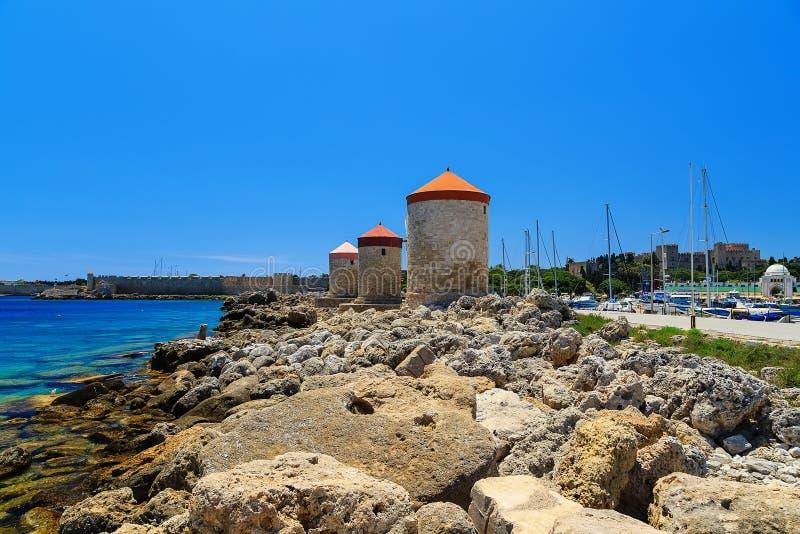 Mandraki hamnväderkvarnar på ön av Rhodes Greece solig dag arkivbilder