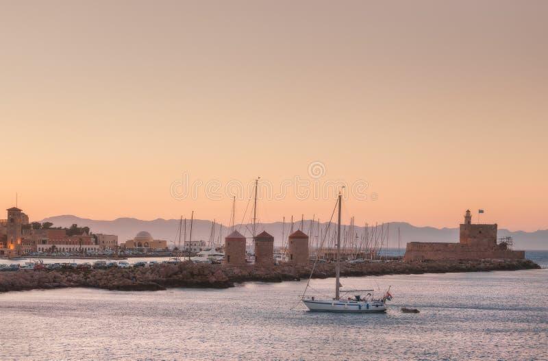 Mandraki port på solnedgången från väderkvarnarna och slotten Ön av Rhodes Grekland arkivbilder